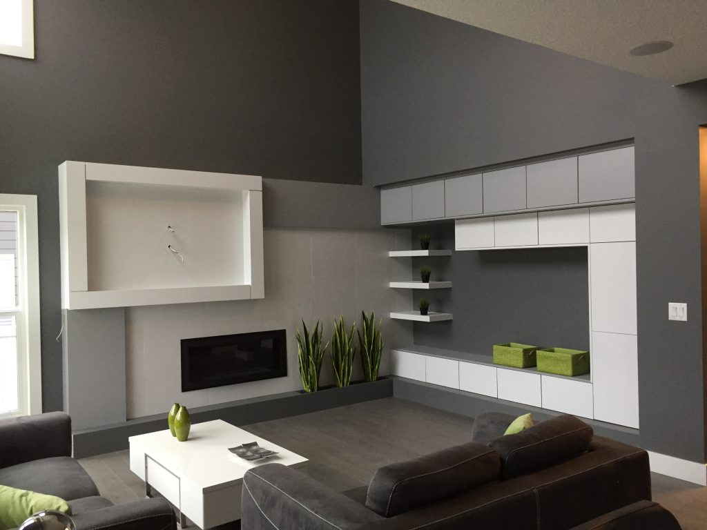 A sharp modern living room incorporating solid grey and green colours.