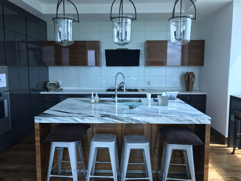 Stunning high gloss walnut kitchen with marble countertops.